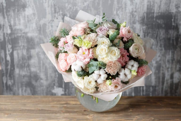 A gorgeous rose bouquet vase placed on top of a wooden table, 11 Beautiful Mother's Day Flower Arrangement Ideas