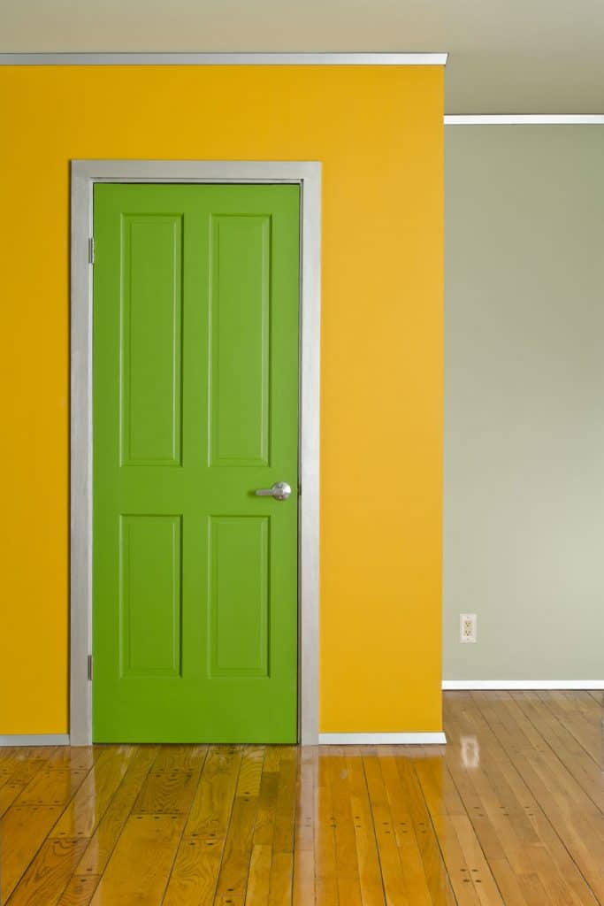 A gorgeous yellow painted wall with a green door with white colored baseboard