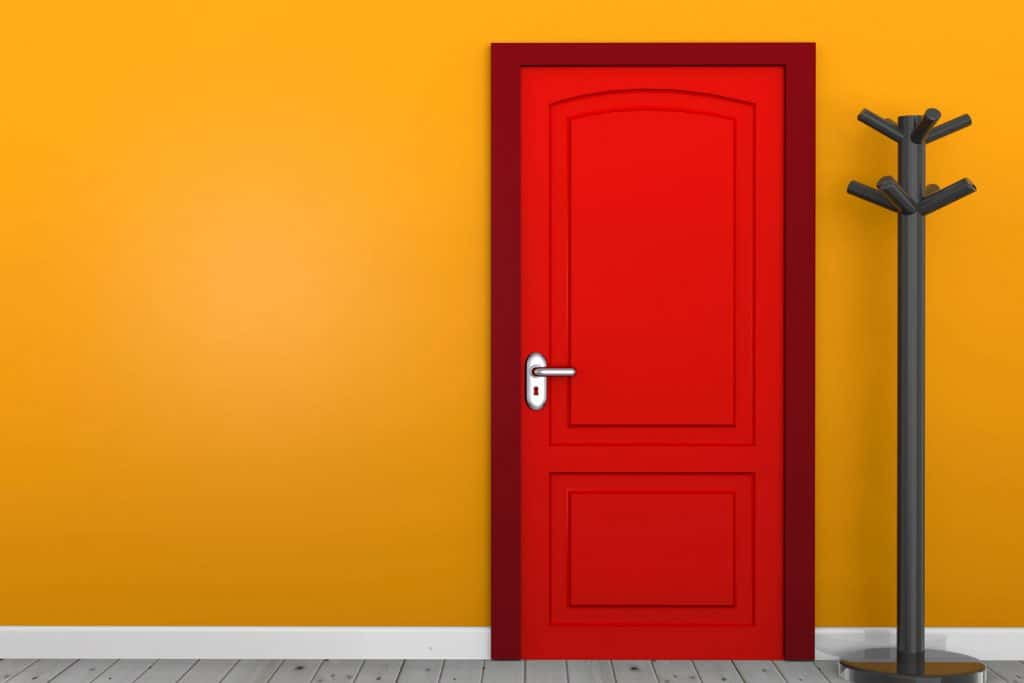 A light orange painted wall with a red door with dark red trim