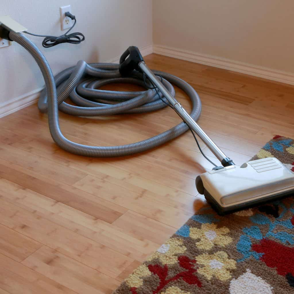A long gray hose of a central vacuum system plugged in to the wall