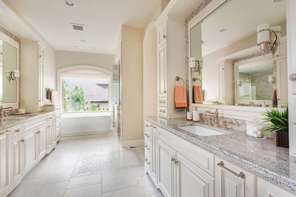 A long span interior of a modern bathroom with white cabinetry and an arched mirror on the bathtub