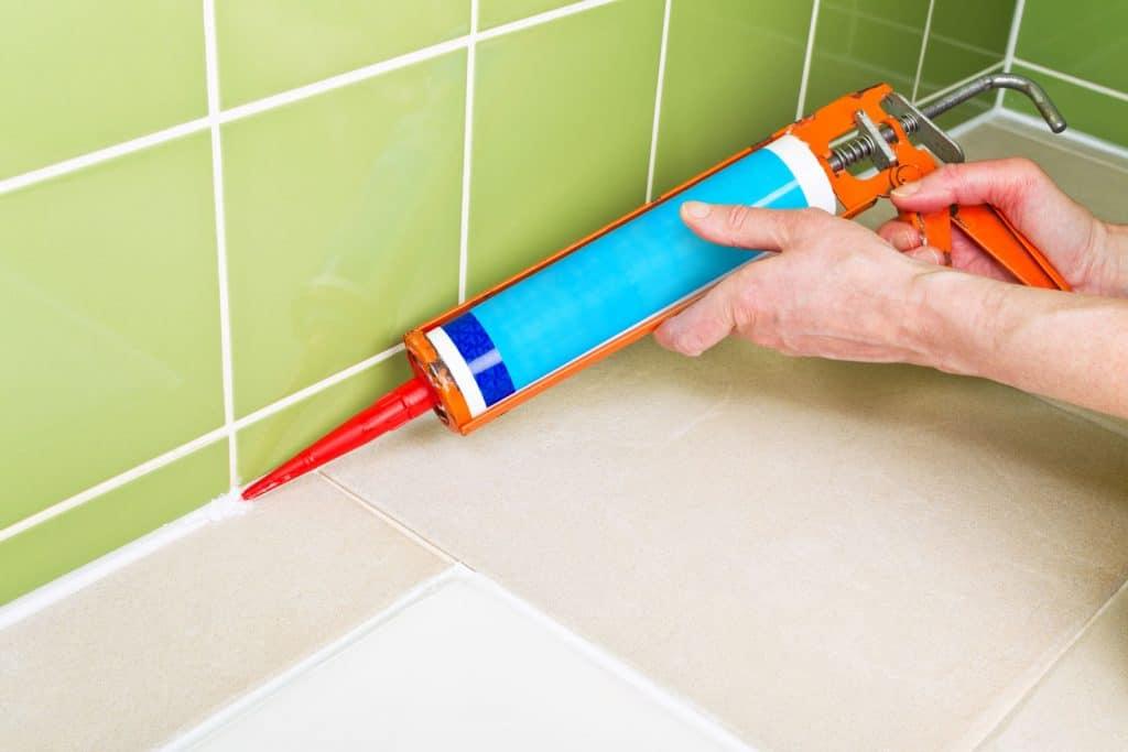 A man caulking the tiles inside the bathroom floor