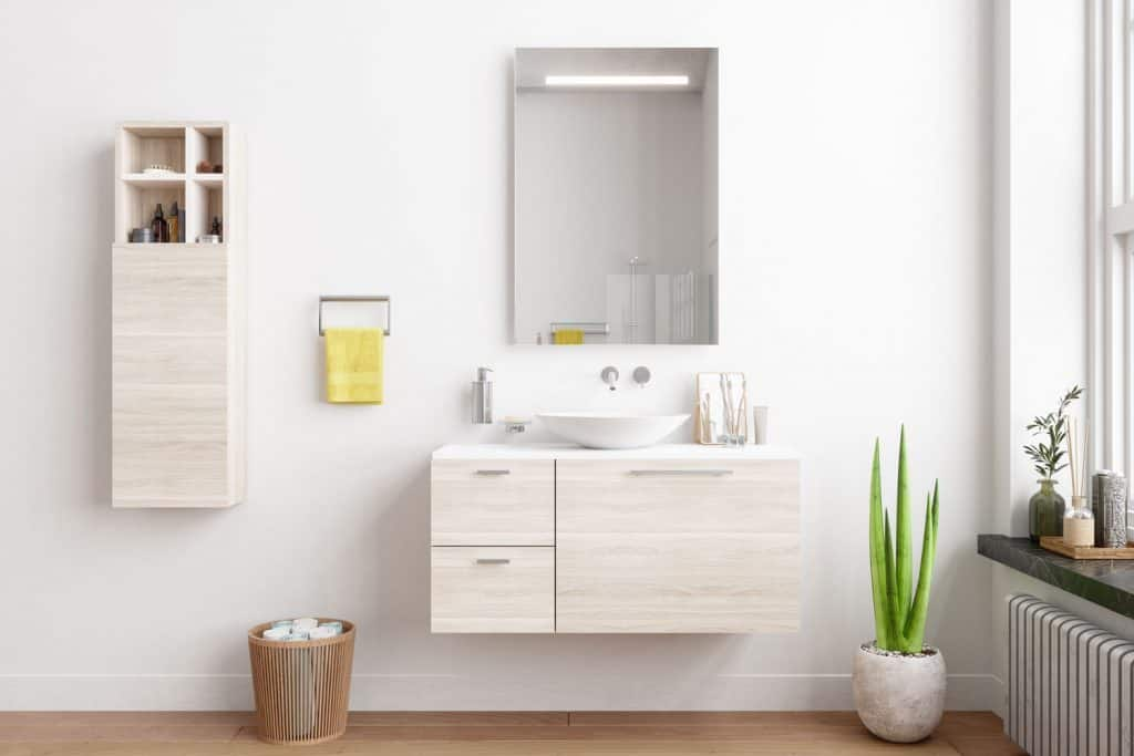 A minimalist inspired bathroom vanity with white painted walls, white cabinetry, and a small mirror