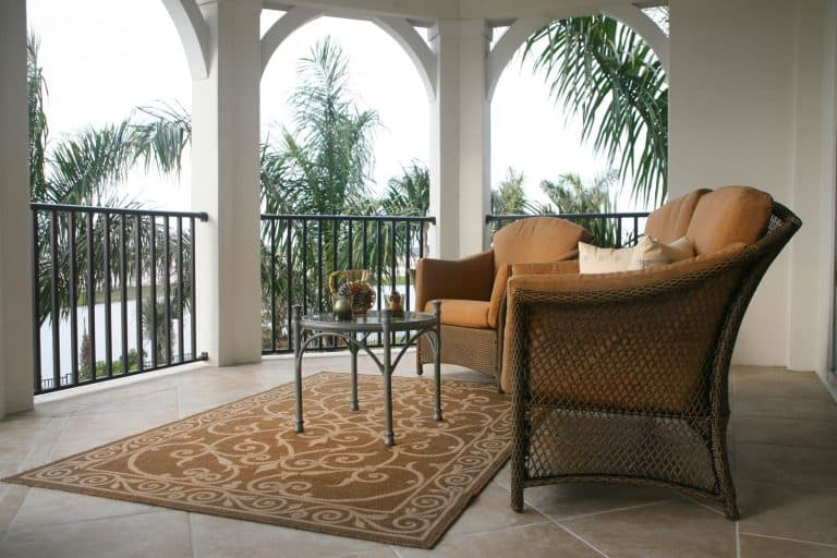 A porch with pattern rug, coffee table and a chair, How Big Should A Porch Rug Be?