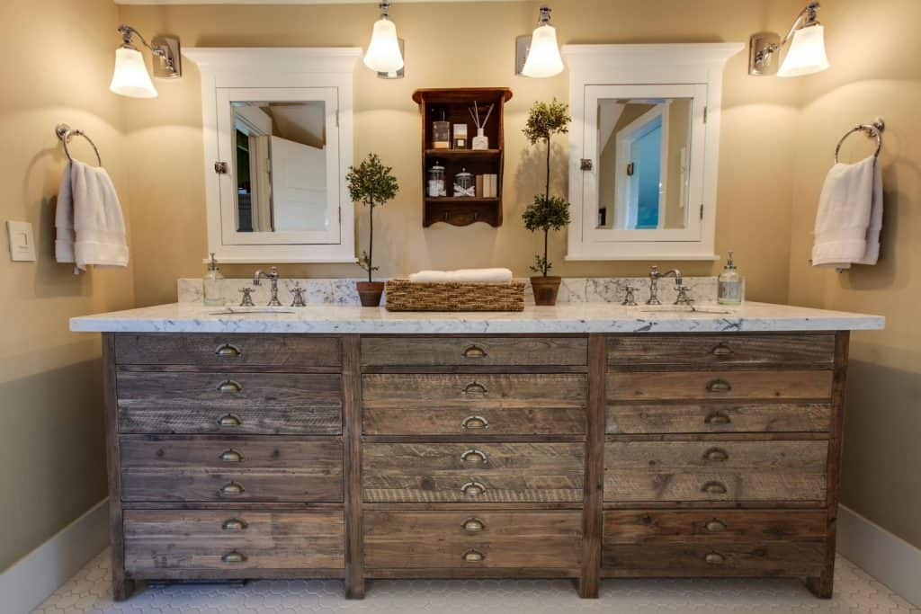 A rustic inspired bathroom cabinet with a marble countertop and two small rectangular mirrors