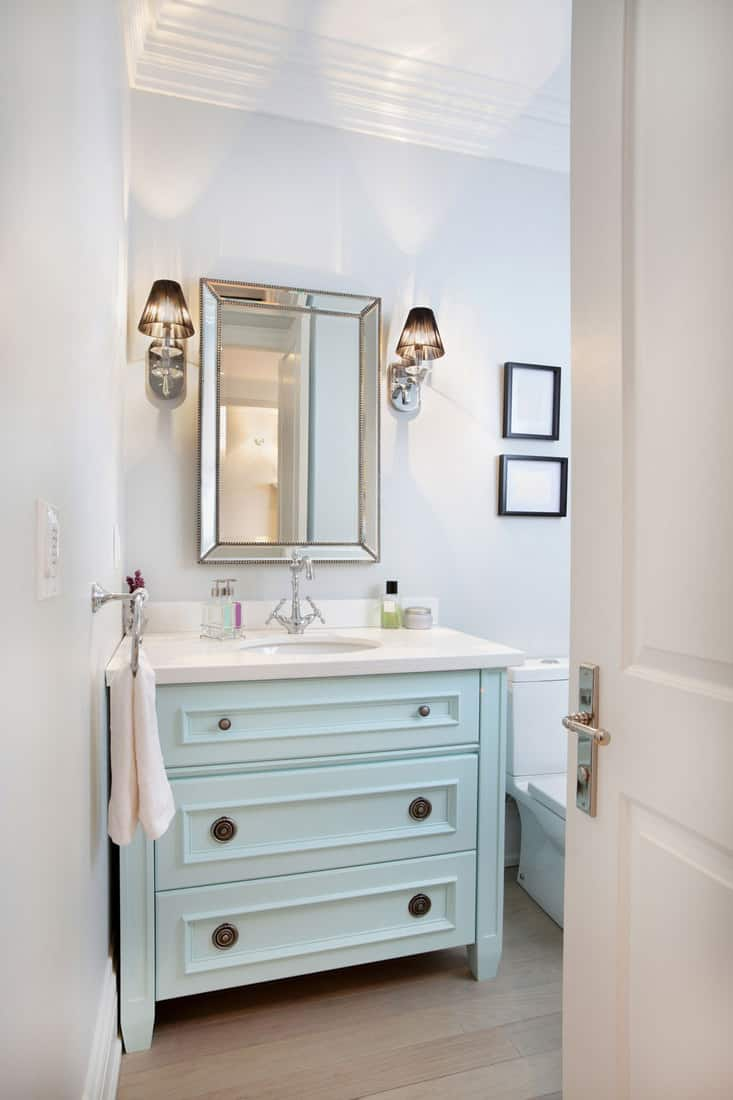 A small light blue painted drawer cabinet below the vanity
