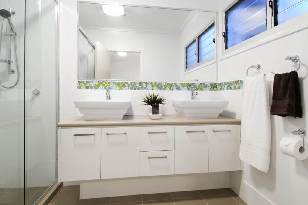 A small modern bathroom with white painted cabinets and two white colored cabinets on top