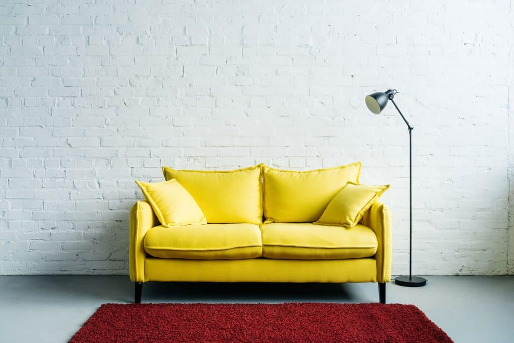 A small yellow colored loveseat sofa with small floor lamp on the side
