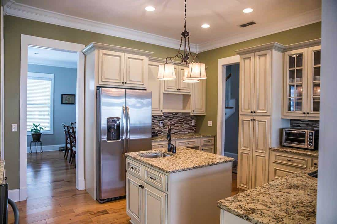 A square shaped green kitchen with granite countertops and lots of cream colored cabinets with storage space