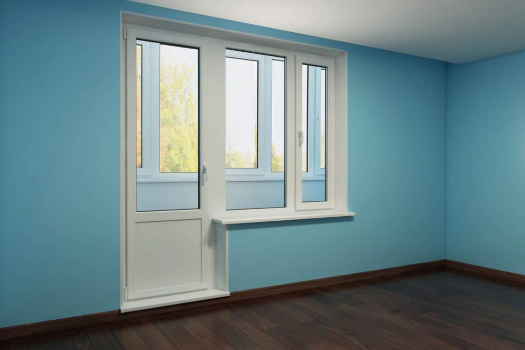 A stunning empty living room with blue painted wall and a small door and window pane painted in white