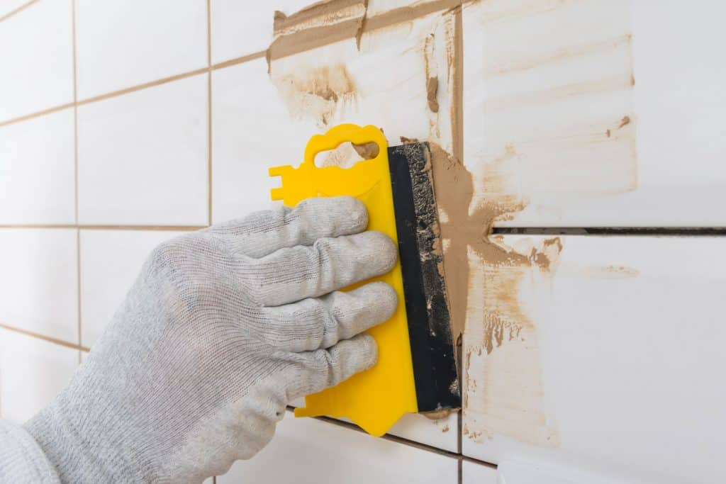A tile setter applying grout to the tiles