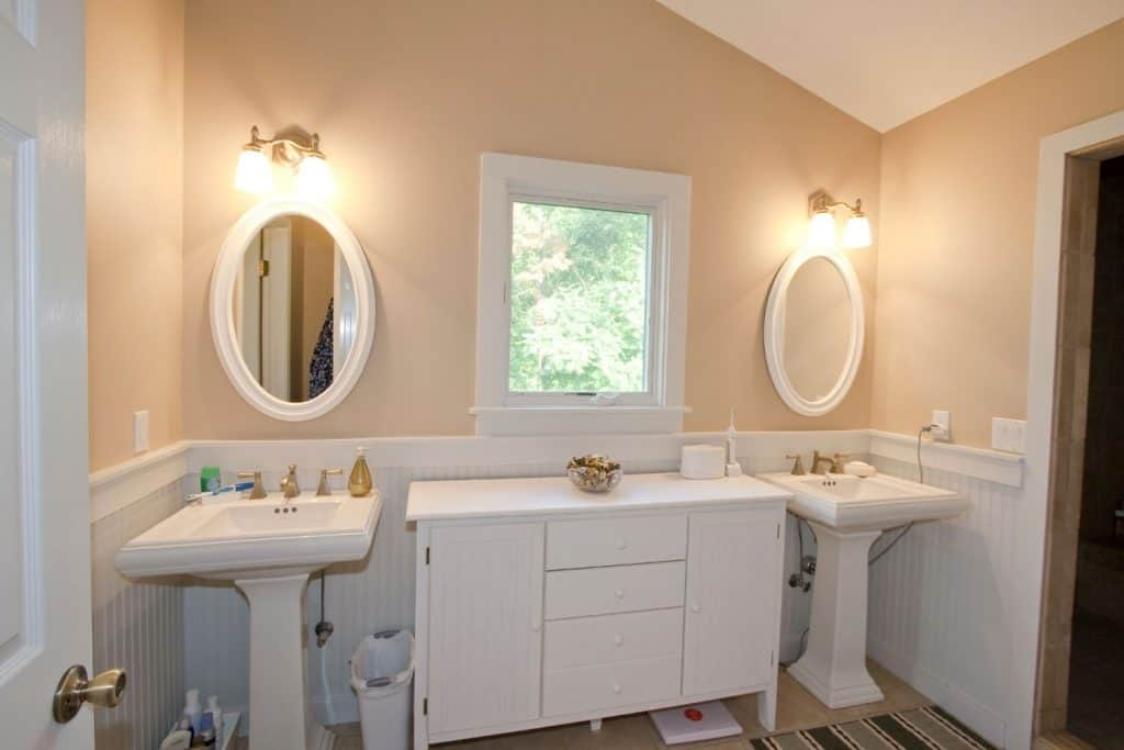 A Victorian inspired bathroom with small elliptical mirrors and two sinks with a cabinet on the middle