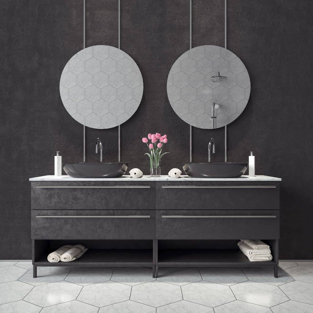 A wonderful placement of a vanity area with round mirrors, black cabinetry, and tulip plants on the countertop