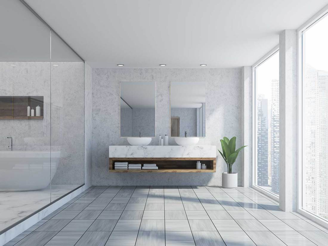 Bathroom interior with marble walls, a white wooden floor, a double sink with two mirrors above it and a bathtub behind glass walls