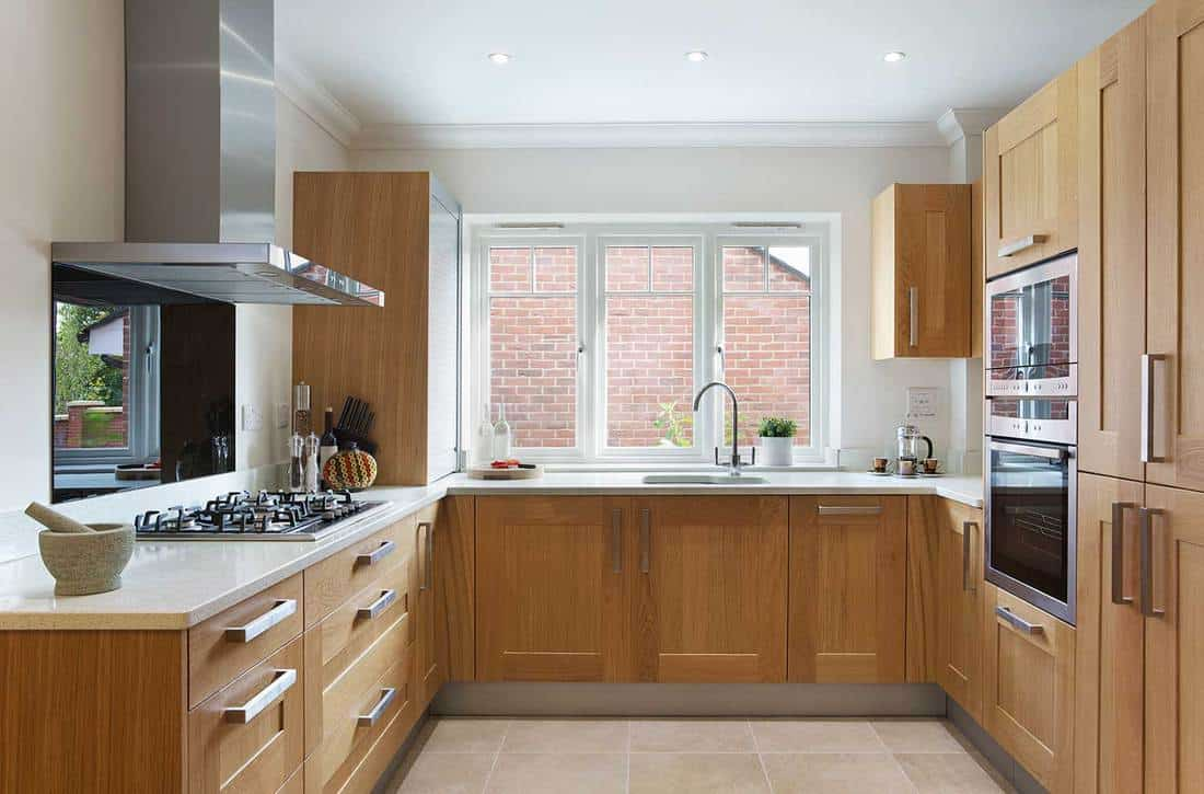 Beautiful kitchen in a modern apartment with oak fitted cupboards and drawers and cream coloured granite work top
