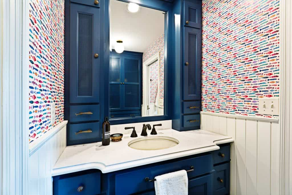 Blue colored cabinetry, white bathroom countertop, and colored walls