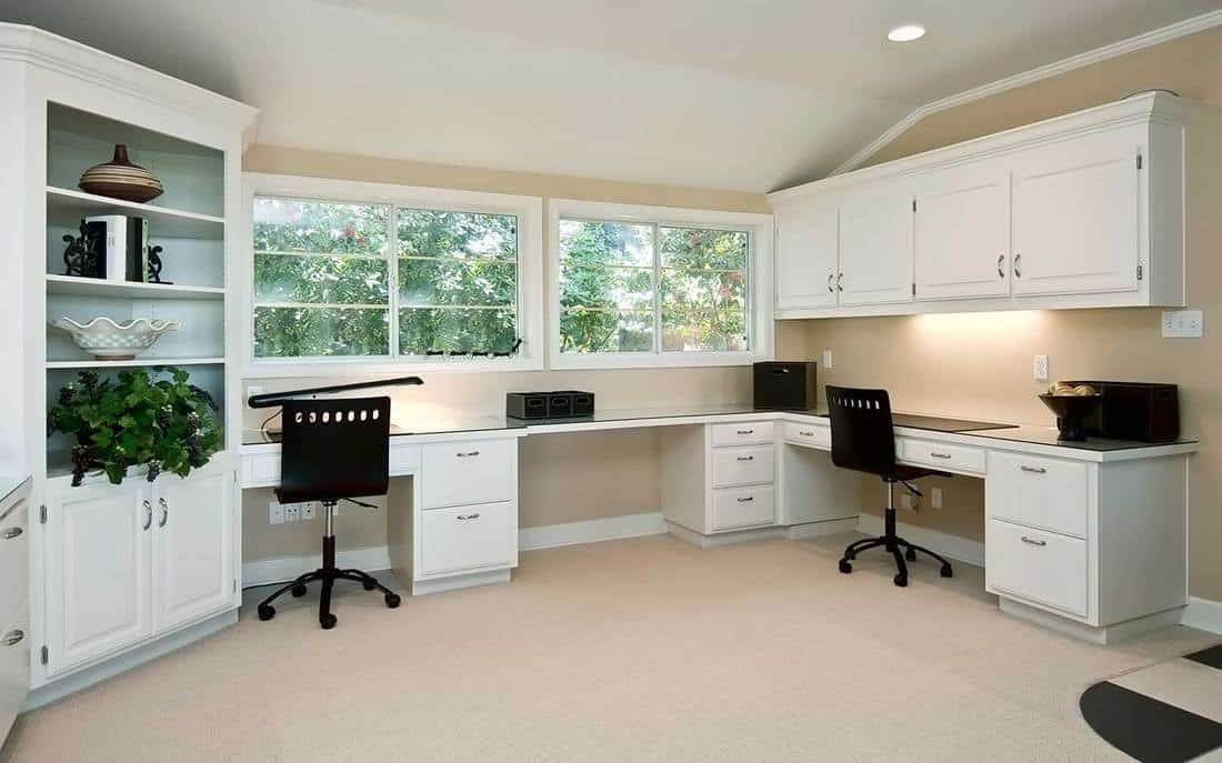 Bright home office with white cabinets and black office chairs
