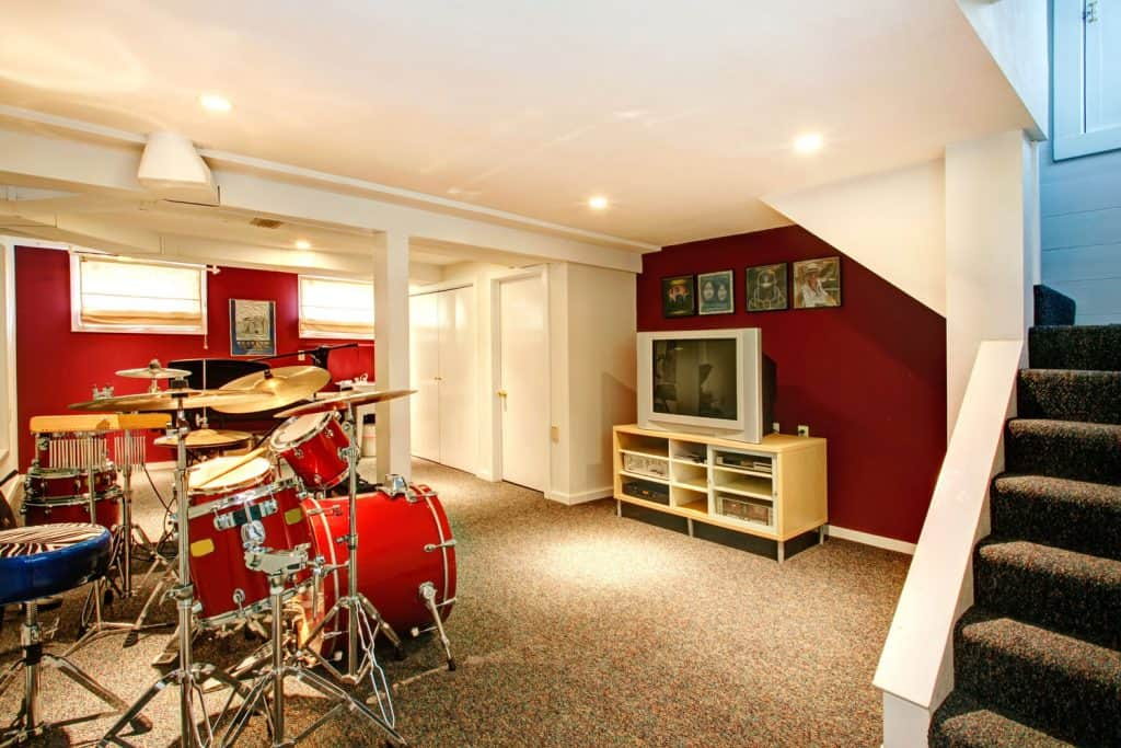 Bright red with white accent walls and white columns music room in the basement