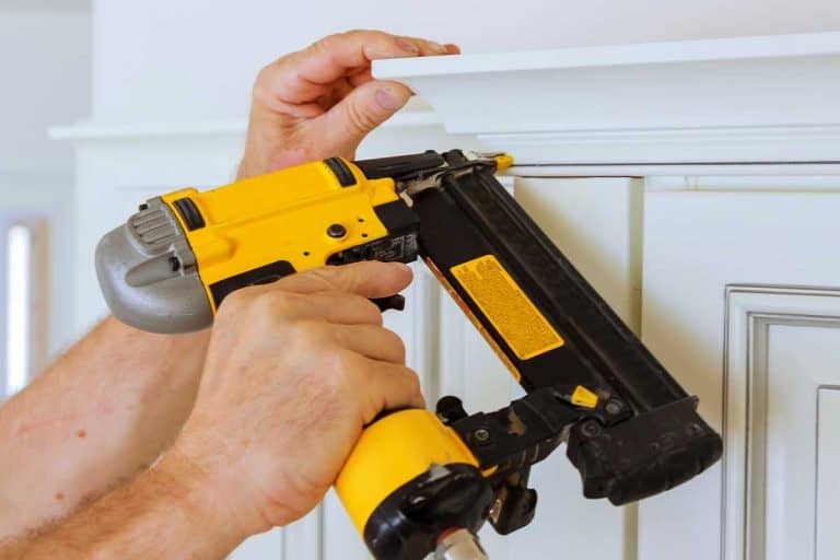 Carpenter brad using nail gun to crown moulding on kitchen cabinets framing trim, How To Nail Crown Molding [4 Steps To Follow]