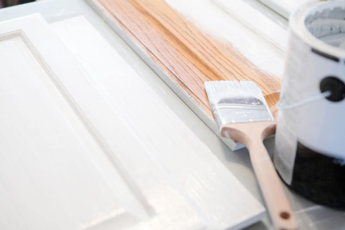 Close up of painting bathroom cabinets white