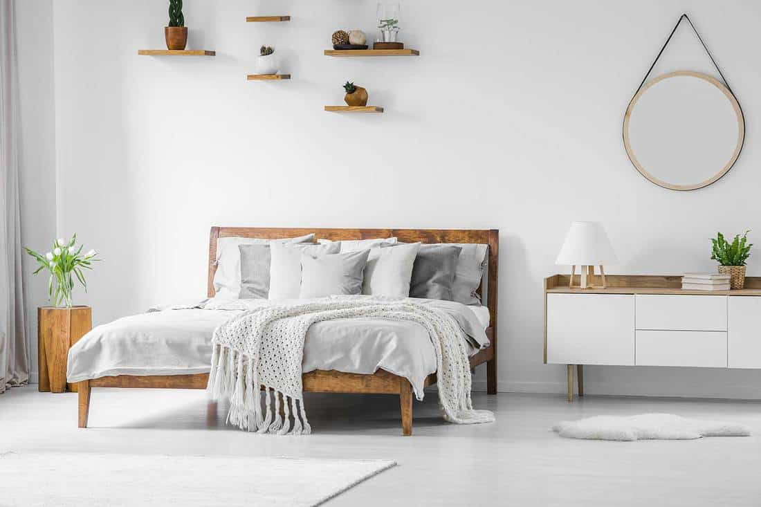 Comfortable big wooden framed bed with linen, pillows and blanket, nightstand beside and round mirror hanging on a white wall in a bright bedroom interior