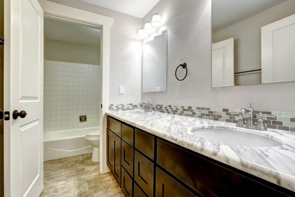 Contemporary interior bathroom with a white granite countertop on the vanity and dark painted cabinets