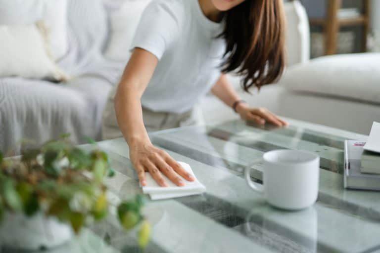 Cropped shot of young Asian woman tidying up the living room and wiping the coffee table surface with a cloth, 15 Ways On How To Prevent Dust In A Room