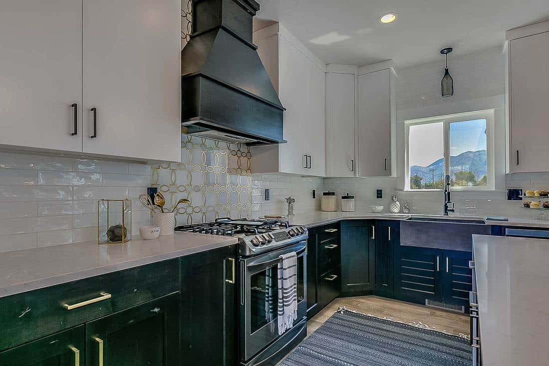 Dark cabinets and waterfall quartz countertops in unique kitchen