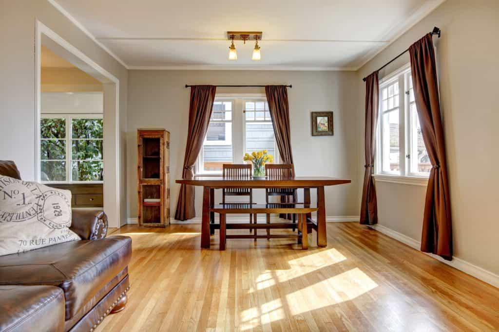 Dining room with brown curtain and hardwood floor.