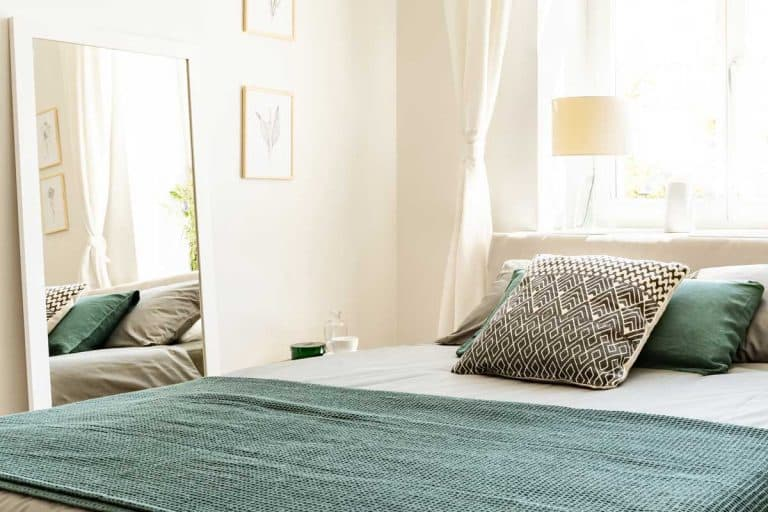 Eco cotton linen and blanket on a bed in nature loving bedroom, Where To Put A Mirror In Your Bedroom? [With Tips According To Feng Shui]