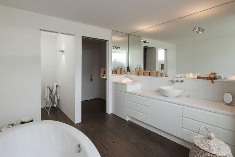 Elegant and white inspired bathroom with white painted cabinets, long span mirror, and a huge white bathtub, How Tall Are Bathroom Cabinets? [Standard Dimensions Explored]