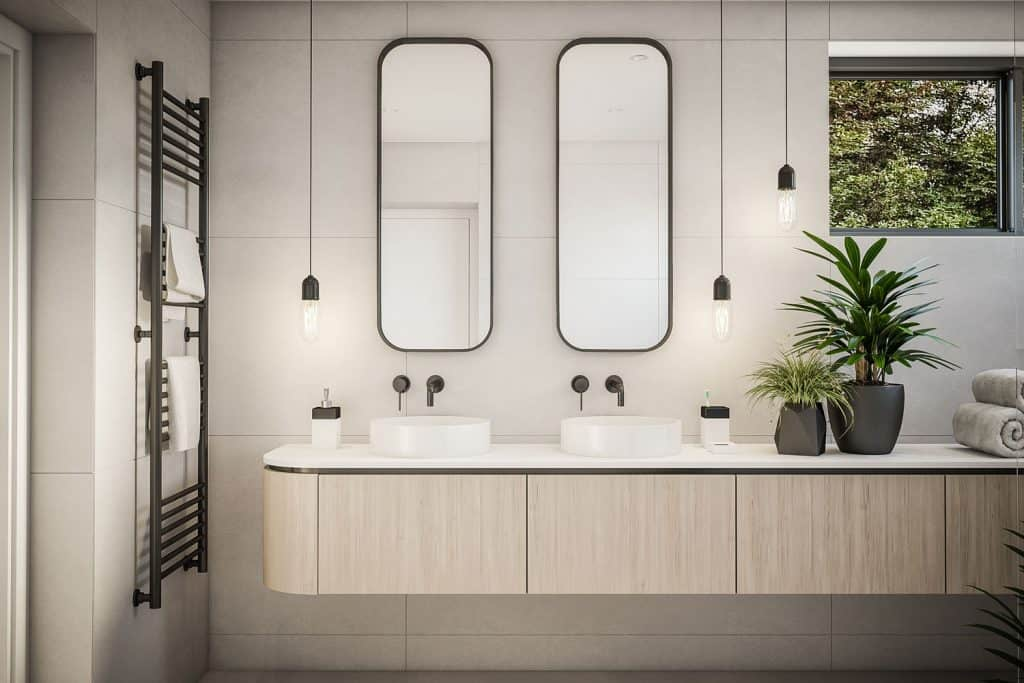 Elegant interior of a contemporary bathroom with plants on the countertop and dangling lamps