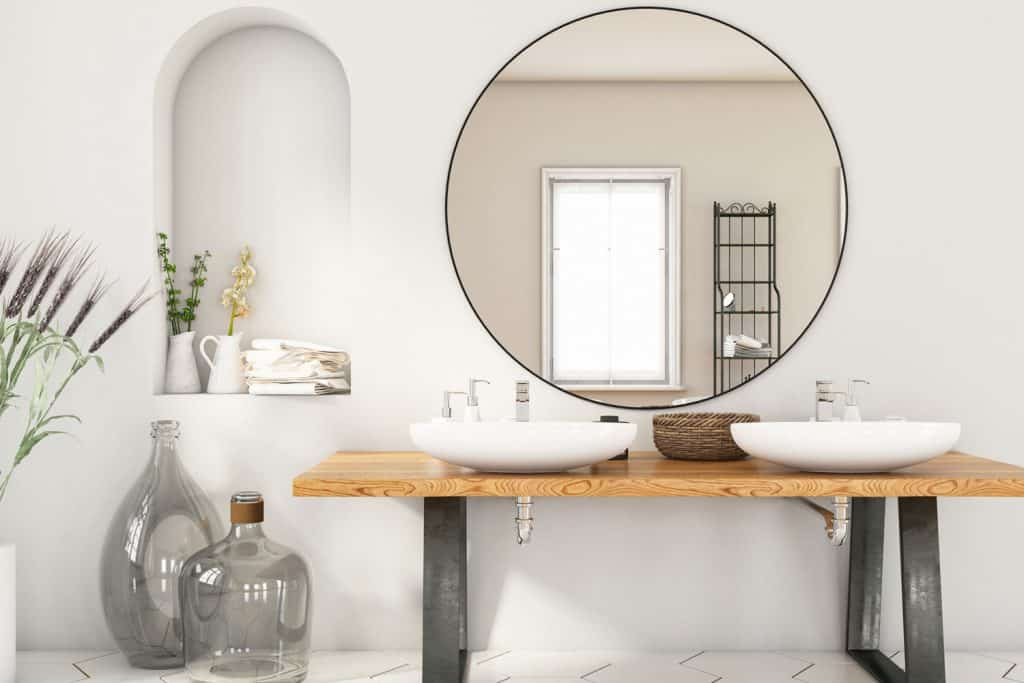 Elegant interior of a contemporary modern great masters bathroom with a huge round mirror