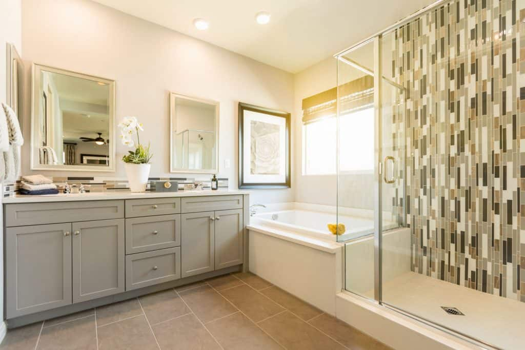 Elegant white inspired masters bathroom with brown tiles, decorative tiled bathroom wall, and a light gray painted cabinetry