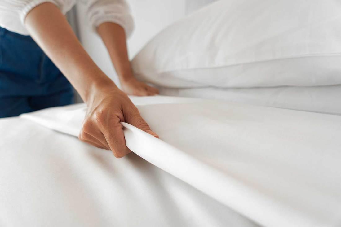 Female hand setting up white bed sheet in bedroom