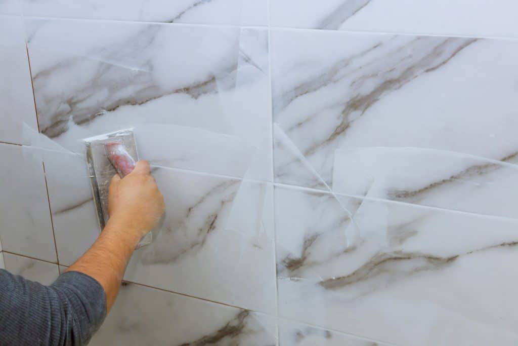 Grouting tiles male hand with the rubber applies grout on a seam between tiles