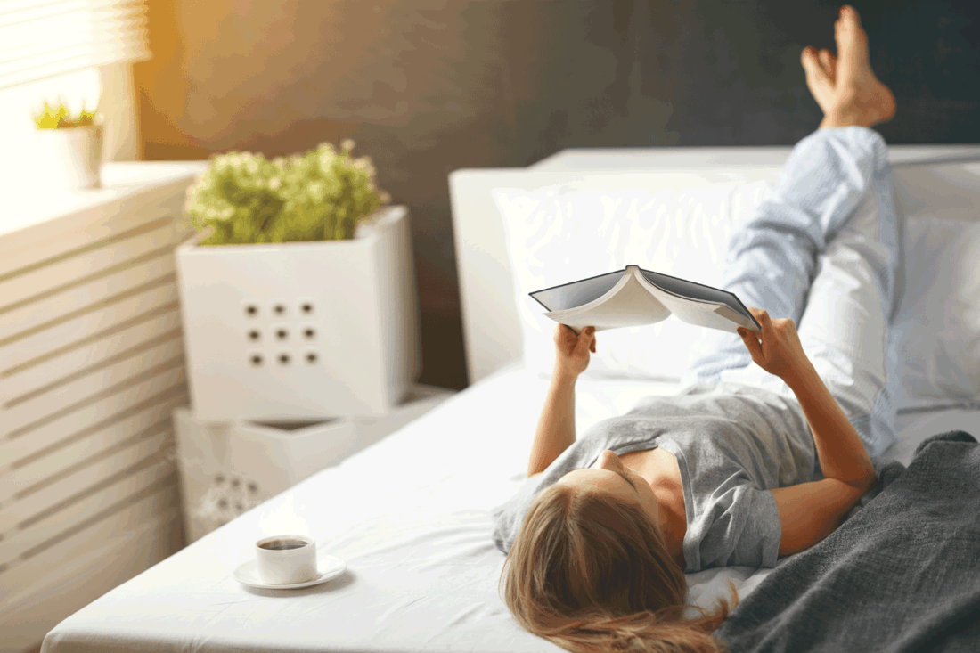 Happy young woman reads book and drinks coffee in bed in morning, reduce stress and anxiety