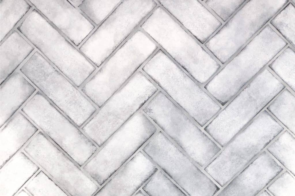 Herringbone tile arrangement on a wall with silver grout