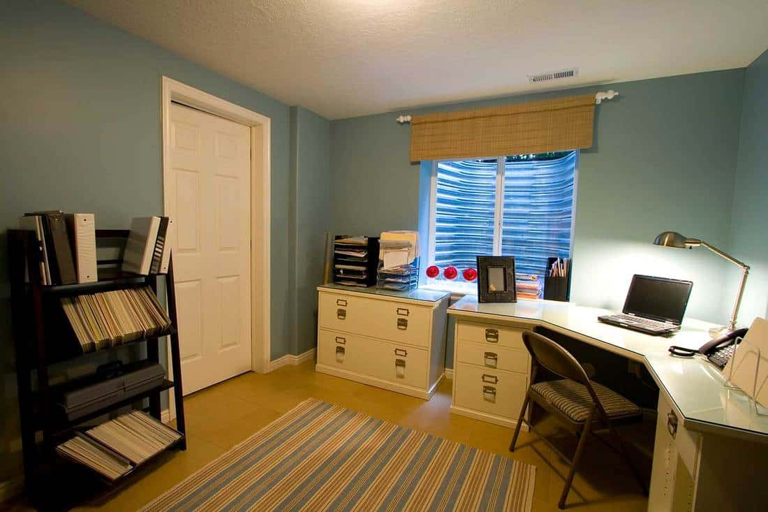 Home office interior with tiled floor, white desk and cabinets