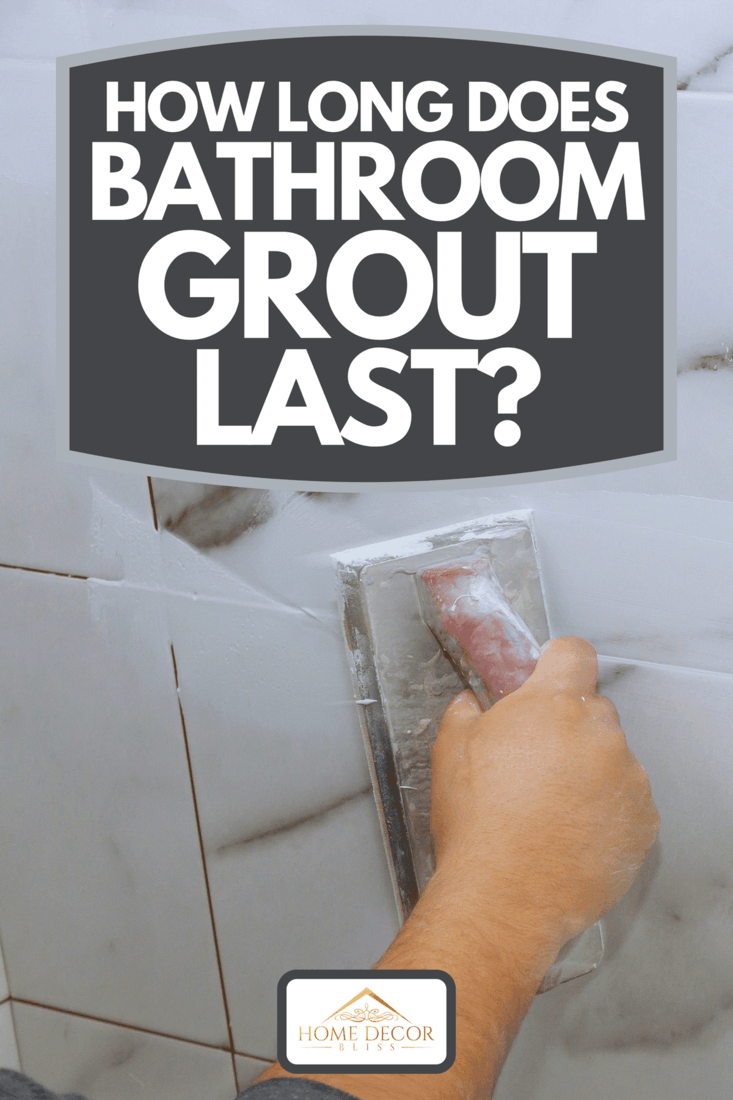 A male hand with the rubber applies grout on a seam between tiles, How Long Does Bathroom Grout Last?