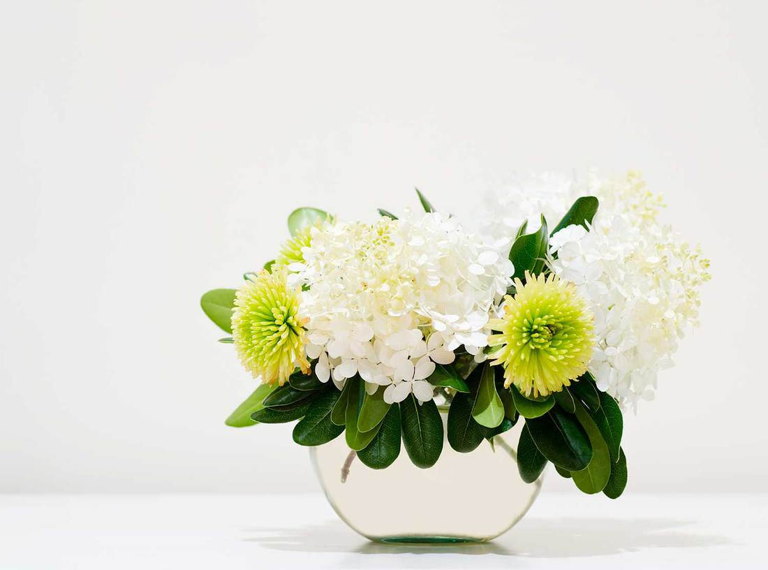 Hydrangea and chrysanthemum blossoms in a glass bowl