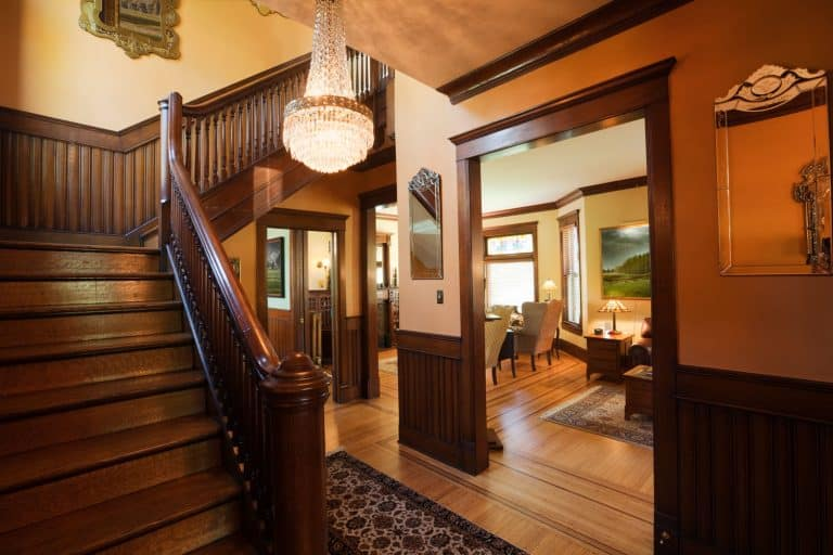 Inside view of a rustic living room with wooden stairs, wooden flooring, and dark wooden baseboard