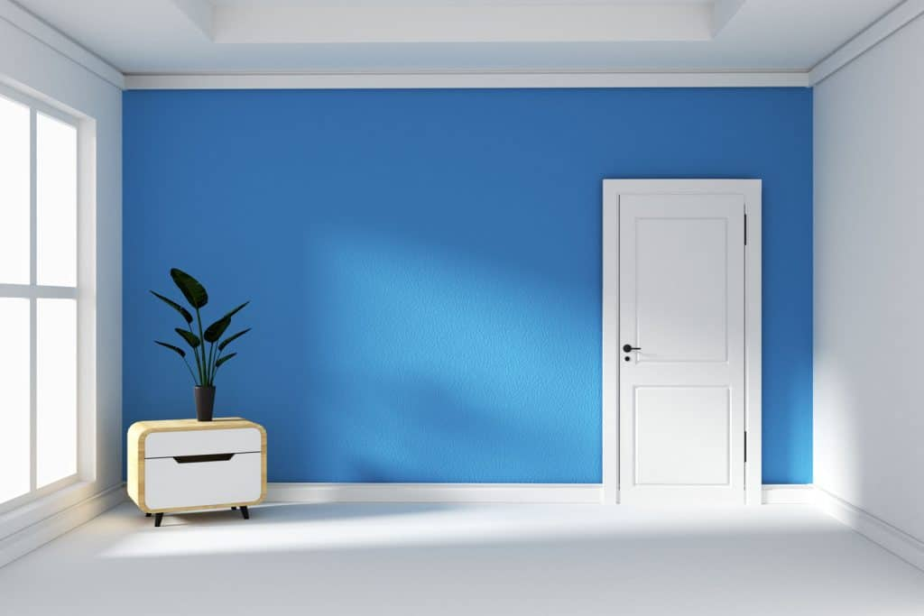 Interior of a blue empty living room with a small cabinet with a plant on top