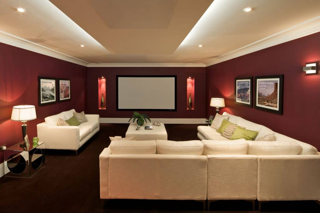 Interior of a contemporary basement with a white ceiling, red walls with huge landscape picture frames, and a huge beige colored sectional sofa