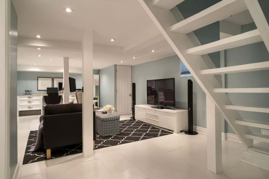 Interior of a modern designed contemporary basement with teal painted walls, black and white area rug, and white tiles