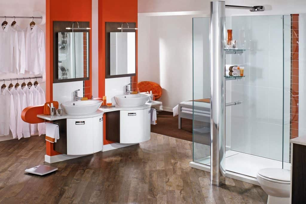 Interior of a retro inspired designed bathroom with red painted vanity walls, glass shower walls, and white stainless steel cabinets