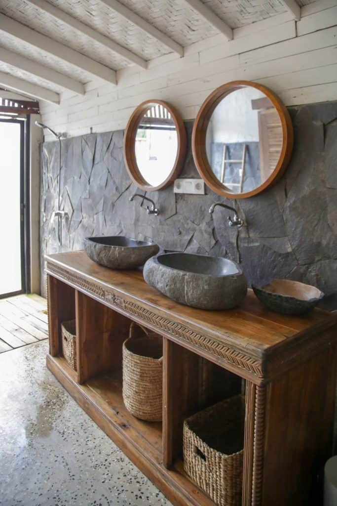 Interior of a rustic inspired great master bathroom with stone cladding on the wall and wooden rustic cabinets