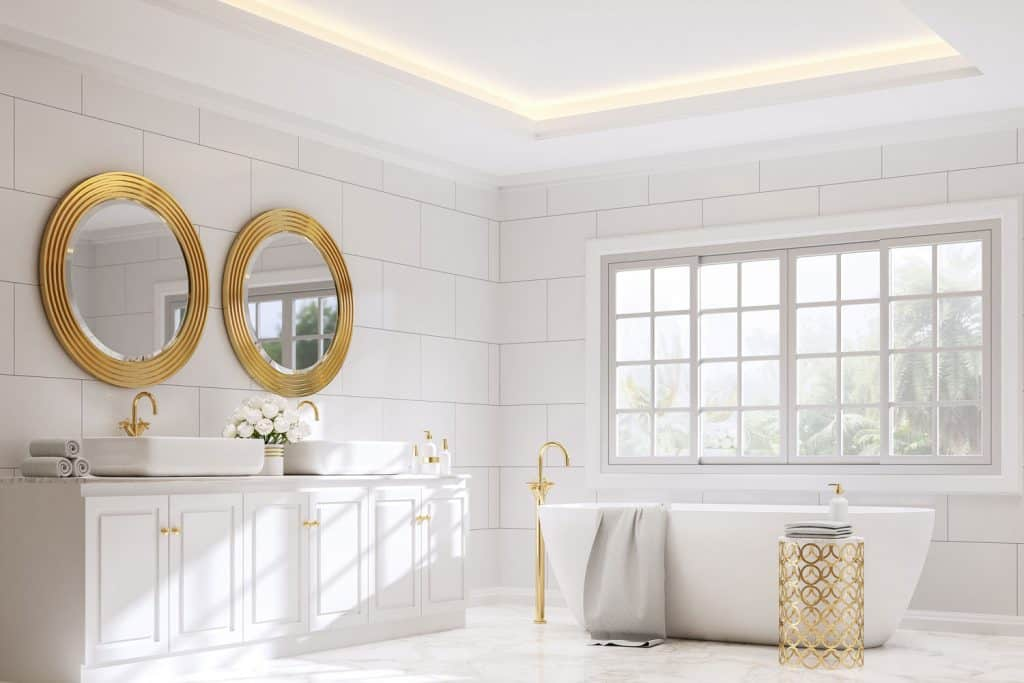 Interior of a spacious white bathroom with tiled walls, white cabinetry, and two round golden framed mirrors