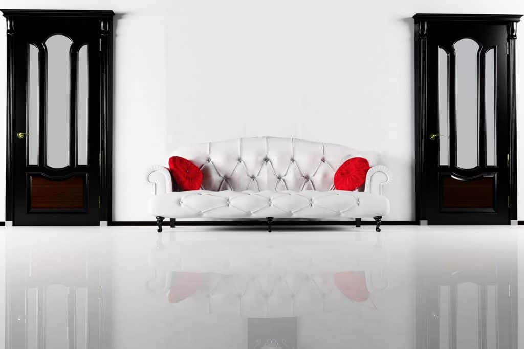 Interior of an elegant living room with a white painted wall, white sofa with red thro pillows and and black painted doors
