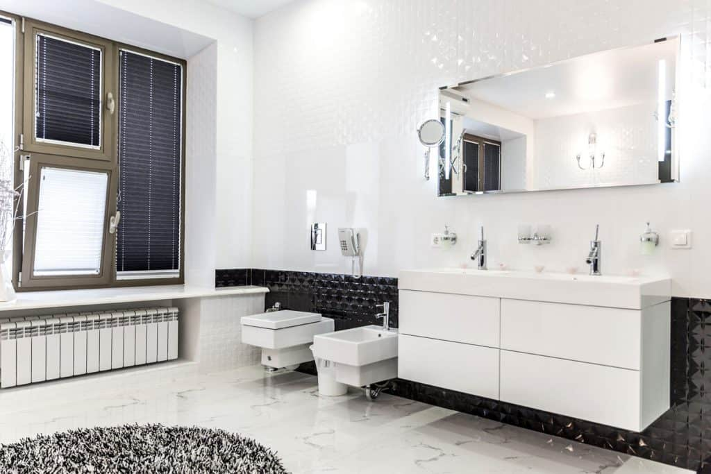 Interior of an ultra modern bathroom with white colored walls, a beautiful vanity with white stainless steel cabinets and black tiled baseboard